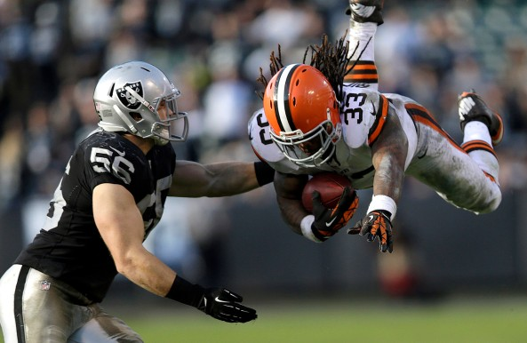 Cleveland Browns running back Trent Richardson leaps in front of Oakland Raiders linebacker Miles Burris.