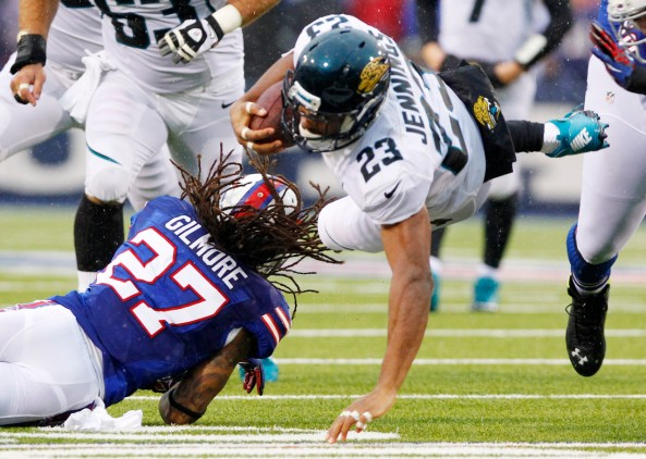 Jacksonville Jaguars' Rashad Jennings (23) dives over Buffalo Bills cornerback Stephon Gilmore (27) for extra yards during the first half of an NFL football game Sunday, Dec. 2, 2012 in Orchard Park, N.Y. Jennings was hurt on the play