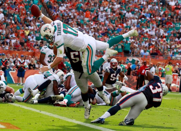 Miami Dolphins quarterback Ryan Tannehill (17) leaps for a touchdown over New England Patriots defensive end Rob Ninkovich (50) during the first half of an NFL football game, Sunday, Dec. 2, 2012, in Miami