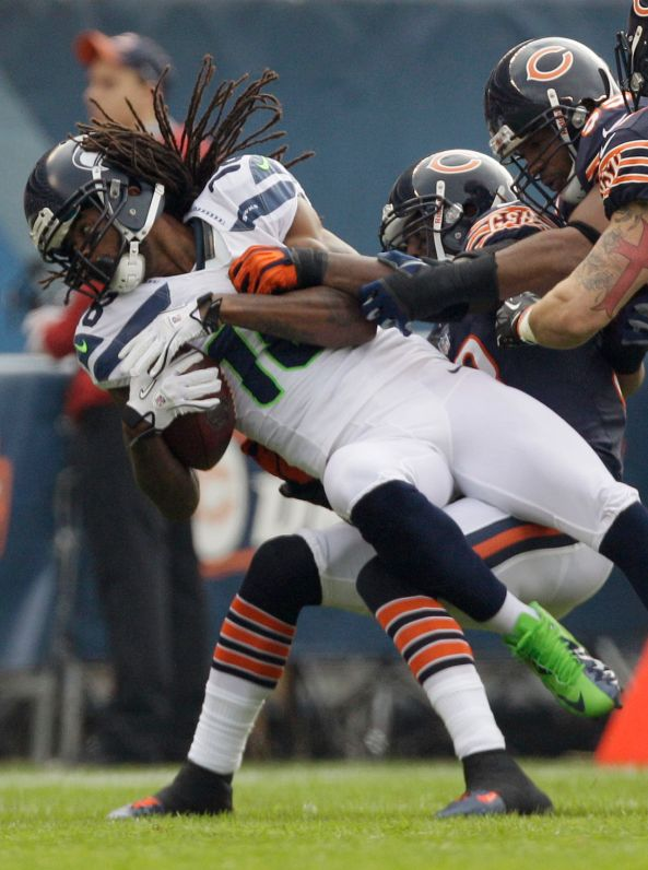 Seattle Seahawks wide receiver Sidney Rice (18) is tackled by Chicago Bears cornerback Charles Tillman (33) and linebacker Lance Briggs, right, in the first half of an NFL football game in Chicago, Sunday, Dec