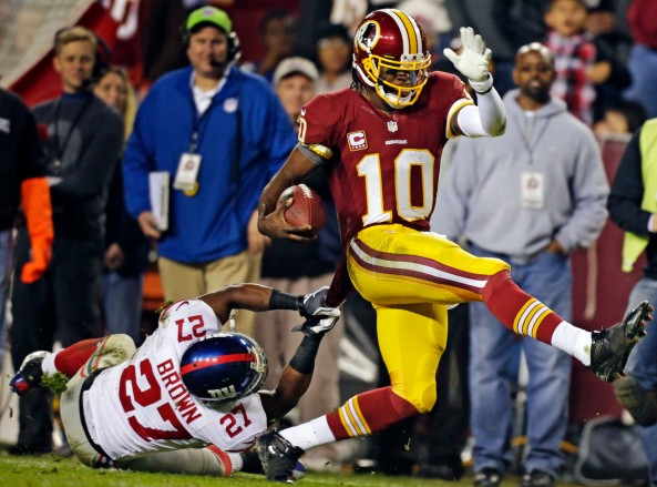 Washington Redskins quarterback Robert Griffin III (10) is pulled down by New York Giants strong safety Stevie Brown (27) during the second half of an NFL football game in Landover, Md., Monday, Dec. 3, 2012. (AP Photo